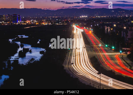 Light trails from busy traffic on Lincoln Boulevard, water reflecting the sky in Ballona Wetlands, and the Santa Monica Mountains in the background af - Stock Photo