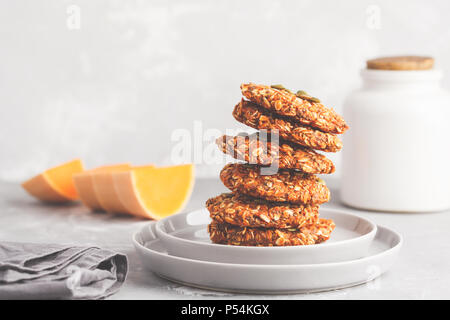 Stack of natural oatmeal pumpkin cookies on a gray plate, halloween food, vegan food concept. - Stock Photo