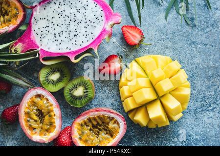 Mango, pitaya, kiwi, strawberry and passion fruit. Tropical fruits on concrete background - Stock Photo