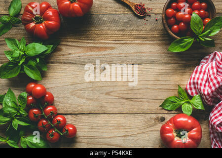 Rustic food background. Heirloom tomatoes, spices and basil on wood. Top view with copy space for text - Stock Photo