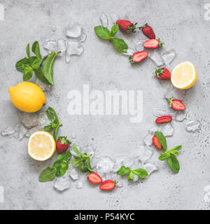 Mint, ice, strawberries and lemon. Refreshing summer lemonade ingredients as a wreath on grey concrete background with copy space for text - Stock Photo