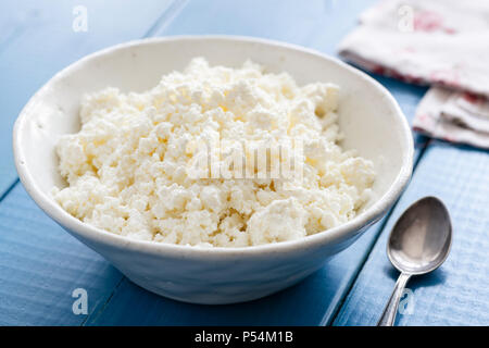 Ricotta or cottage cheese in white bowl on blue table. Healthy dairy product. Tvorog or farmer's cheese. - Stock Photo