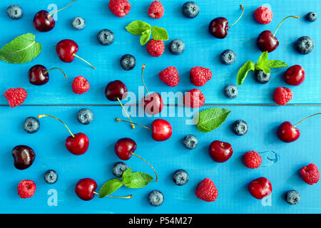 Berries on blue background, flat lay. Berry pattern on blue wood background. Raspberry, sweet cherry, blueberry and mint leaf pattern - Stock Photo