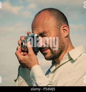 bearded tourist man photographs an old film camera. Portrait of a bearded man with a camera. - Stock Photo