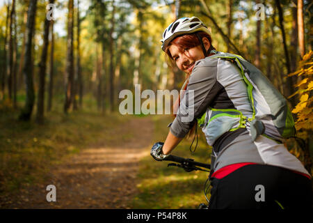 Photo of woman wearing helmet on bicycle in autumn forest - Stock Photo