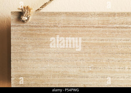 Abstract composition of small wooden board hanged on wall with ropes. - Stock Photo