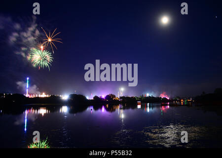Newport, Isle of Wight, UK. 24th June, 2018. Fireworks and a near full moon herald the end of the last day of the Isle of Wight Festival as the Sunday night headliner band 'The Killers' play on the main stage, seen in the distance in bright lights. Photograph taken from the banks of the River Medina in Newport, Isle of Wight, June 24th 2018. Credit: Matthew Blythe/Alamy Live News - Stock Photo