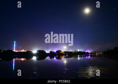 Newport, Isle of Wight, UK. 24th June, 2018. Fireworks and a near full moon herald the end of the last day of the Isle of Wight Festival as the Sunday night headliner band 'The Killers' play on the main stage, seen in the distance in blue lights. Photograph taken from the banks of the River Medina in Newport, Isle of Wight, June 24th 2018. Credit: Matthew Blythe/Alamy Live News - Stock Photo