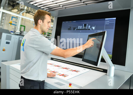 Wiesloch, Germany. 08th June, 2018. An employee operating the control unit a digital printing machine of the type 'Primefire 106' in the workshop of Heidelberger Druckmaschinen AG ('Heidelberg printing machines'). The company is releasing its figures for the past business year on Tuesday (12 June). Credit: Uwe Anspach/dpa/Alamy Live News - Stock Photo