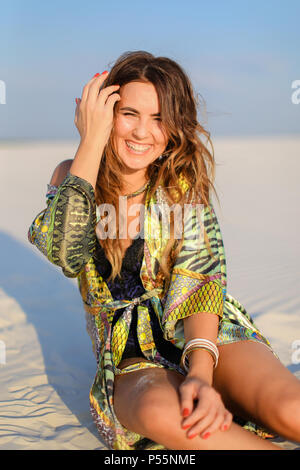 Young happy female person wearing green beach robe and sitting o - Stock Photo