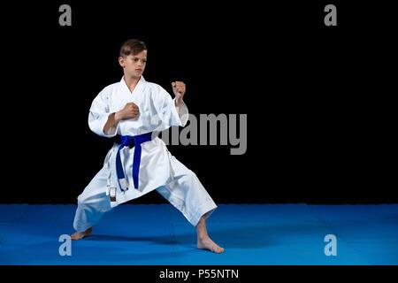 Pre-teen boy doing karate on a black background - Stock Photo