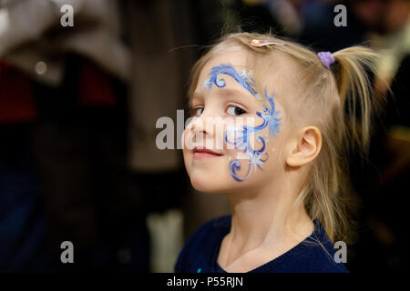 Cute little blond girl with face painting. Blue abstract snowflake pattern by watercolor on kids face. Adorable child with colorful drawings. Children - Stock Photo
