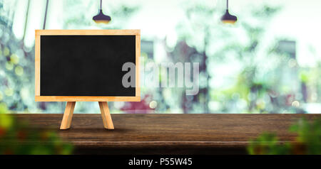 Blackboard menu on dark brown wooden table top with blurred window of coffee shop, Mock up template for display or montage of your design,Banner for a - Stock Photo