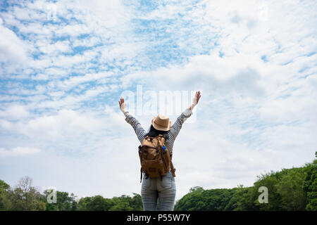 Happy young traveler woman backpacker raised arm up to sky enjoying a beautiful of nature panorama view,Freedom wanderlust travel - Stock Photo