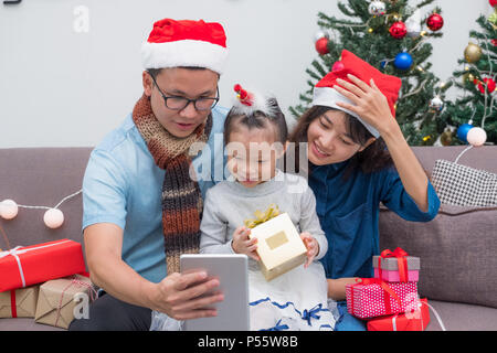 Happy family Asia selfie with tablet at sofa,father and mother wear santa claus hat give Christmas gift box to child at house xmas party,Holiday celeb - Stock Photo