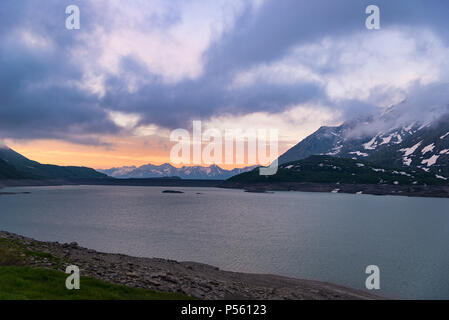 Scenic sky clouds at sunrise, lake and snowcapped mountain, cold winter, fjord nord landscape - Stock Photo