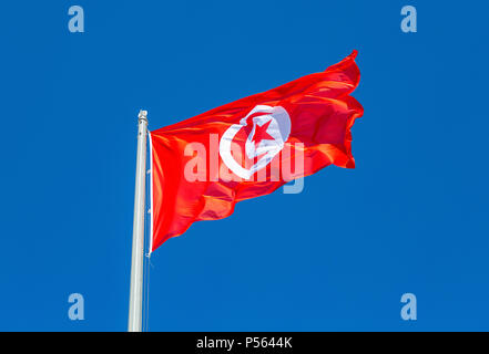 Flag of Tunisia waving in the wind against the blue sky - Stock Photo