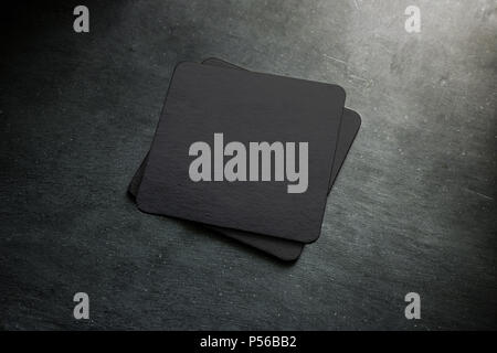 Blank black beer coaster stack mock up, top view, lying on the textured background. Squared clear can mat design mockup isolated. Quadrate cup rug display - Stock Photo
