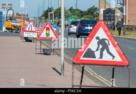 Temporary traffic lights at roadworks on a road in the UK. - Stock Photo