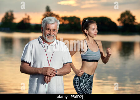 Senior man and young girl running near lake in the evening. Outdoor activities, healthy lifestyle, strong bodies, fit figures. Stylish, modern sportswear. Different generations. Sport, yoga, fitness. - Stock Photo