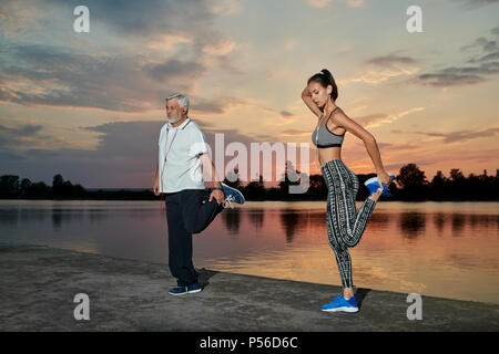 Senior man and young girl stretching muscles near lake on sunset. Fitness, yoga, crossfit exercises. Fit, strong bodies, healthy lifestyle. Different generations. Outdoors workout on fresh air. - Stock Photo