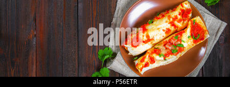Homemade chicken enchiladas in dish on wooden table. Top view - Stock Photo