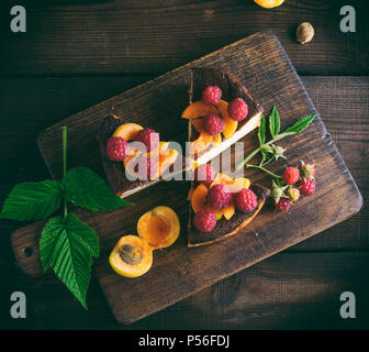 pieces of cottage cheese pie with strawberries and apricots on a brown wooden board, top view - Stock Photo
