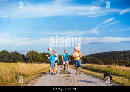 Family walking their dog on a dirt path - Stock Photo