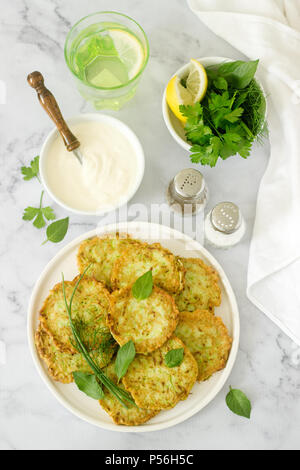 Pancakes from zucchini, served with sour cream or yogurt and various herbs. Useful vegetarian food. Selective focus. - Stock Photo
