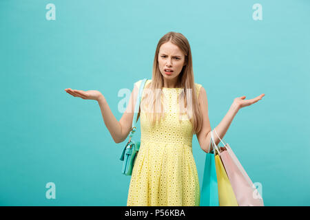 Shoping and Sale Concept: beautiful unhappy young woman in yellow elegant dress with shopping bag. - Stock Photo