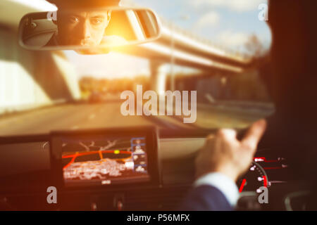 Man driving car and looking into rear view - Stock Photo