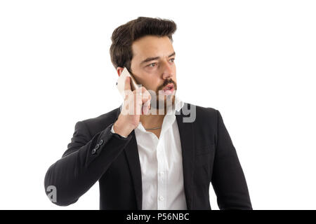 Businessman is looking to the side. He's talking on the phone. Concept of communication, telephony. Beautiful bearded person is wearing black jacket a - Stock Photo