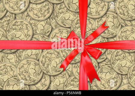 Motley background from chaotically scattered Australian one dollar coins gift tied red bow abstract seamless patterns background. - Stock Photo