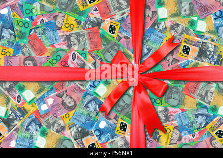 Motley background from chaotically scattered Australian dollar banknotes gift tied red bow abstract seamless geometrical patterns background. - Stock Photo