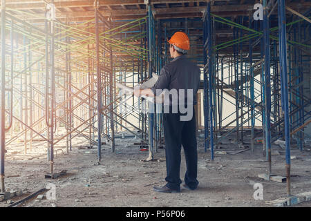 Engineer with blueprint in building construction site - Stock Photo