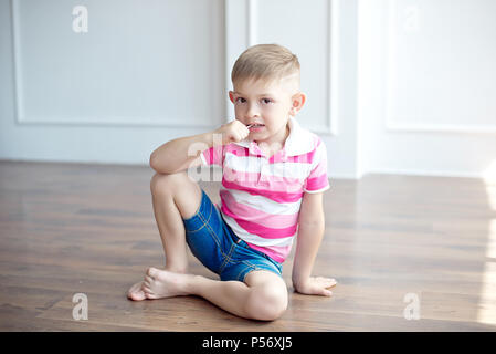 little cute boy with modern haircut sitting on the floor in big white room - Stock Photo