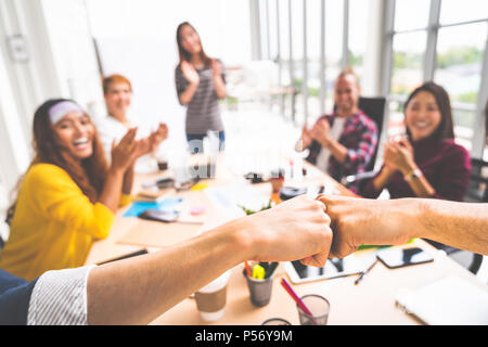Business partners or men coworkers fist bump in team meeting, multiethnic diverse group of happy colleagues clapping hands. Teamwork concept - Stock Photo
