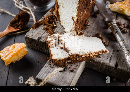 soft homemade cheese wrapped in ground coffee and a cup of coffee with milk breakfast on a wooden table - Stock Photo