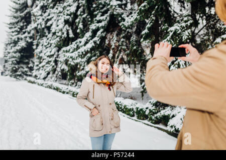 Young couple in love rest in the park winter. A man holds mobile phone in hands and takes a photo of girlfriend against the background of snowcovered  - Stock Photo