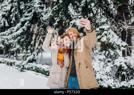 Young couple in love make a joint photo of themselves on a mobile phone. The guy holds a smartphone on his elongated hand and makes a photo, waving ha - Stock Photo