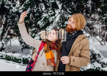 Young couple in love rest in park winter. A man hugs girlfriend, woman holds mobile phone in her hand and takes photo of herself. People use smartphon - Stock Photo
