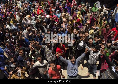 Kulgam, Kashmir, India. 25th June, 2018. Pro-freedom and pro-Islam slogans raised by the mourners as the body of Lashkar-e-Toiba commander Shakoor Ahmad Dar is being marched towards the local graveyard at his native village in Devsar area of South Kashmir's Kulgam district on Monday, 25 June 2018 in Indian- Administered-Kashmir.Thousands of people took part in the last rites of Dar. Rebels surfaced during the funeral procession and offered gun salute to slain rebel. Dar along with an associate was killed during a gunfight with government forces in adjoining area of kulgam district while his - Stock Photo