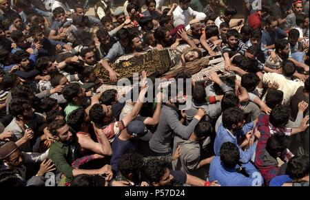 Kulgam, Kashmir, India. 25th June, 2018. Kashmiri mourners carry the body of Lashkar-e-Toiba commander Shakoor Ahmad Dar towards the local graveyard at his native village in Devsar area of South Kashmir's Kulgam district on Monday, 25 June 2018 in Indian- Administered-Kashmir.Thousands of people took part in the last rites of Dar and raised pro-freedom and pro-Islam slogans. Rebels also surfaced during the funeral procession and offered gun salute to slain rebel. Dar along with an associate was killed during a gunfight with government forces in adjoining area of kulgam district while his th - Stock Photo