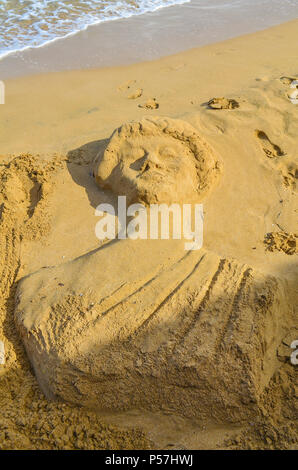 Sand sculpture in the form of an antique statue on the beach. - Stock Photo