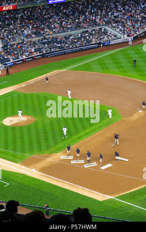The grounds crew groom the infield dirt between innings during a night game at Yankee Stadium, the Bronx, NYC, USA