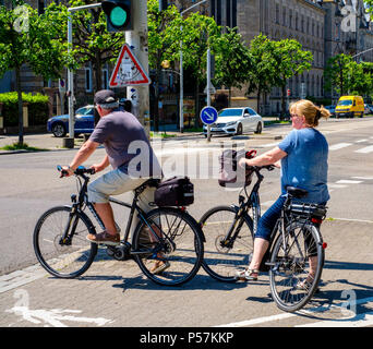 Strasbourg, mature couple of cyclists waiting at traffic light before crossing the street, Alsace, France, Europe, - Stock Photo