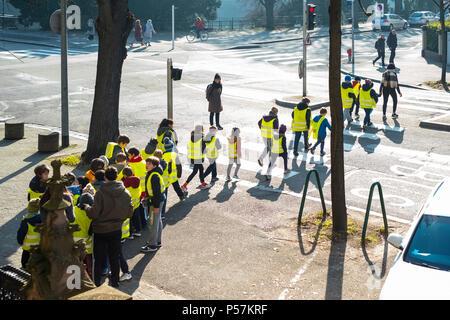 Strasbourg, young schoolchildren wearing yellow hi-vis jackets crossing street on pedestrian crossing, Alsace, France, Europe, - Stock Photo
