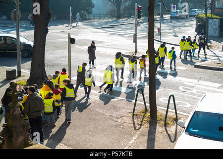 Strasbourg, young schoolchildren wearing yellow hi-vis jackets crossing street on pedestrian crossing, Alsace, France, Europe, - Stock Photo