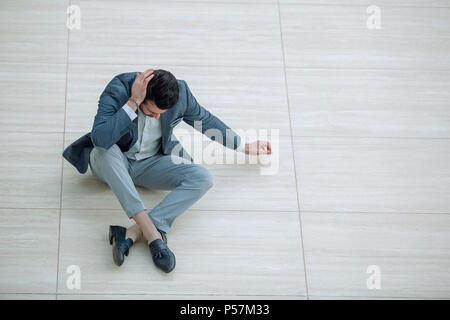 frustrated young businessman sitting on the floor and looking down. - Stock Photo