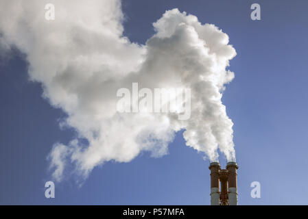 industrial factory pipes smoke at the sun on blue sky - Stock Photo
